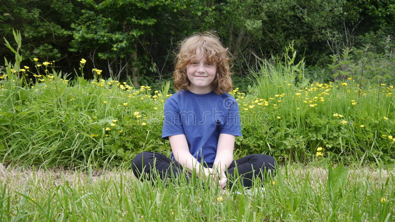 Young girl sitting in a field stock photo