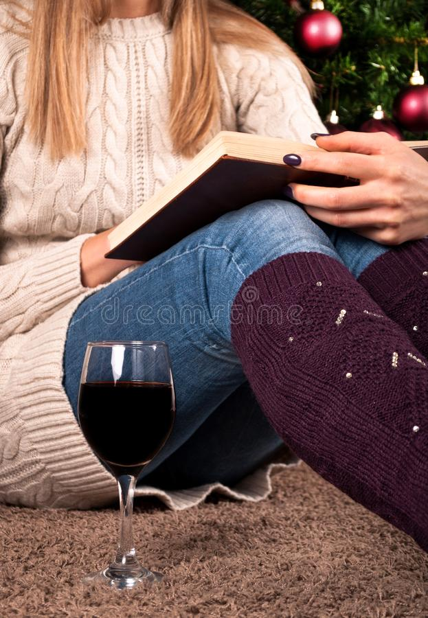 Young girl sitting on floor and reading book next to Christmas tree and coffee cup stock photo