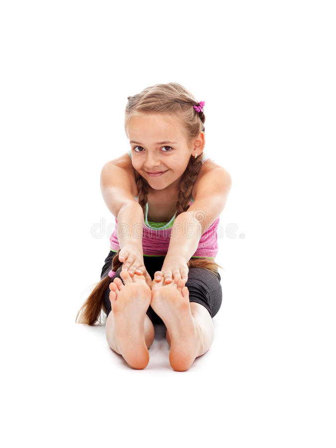 Young girl sitting on the floor and stretching royalty free stock image