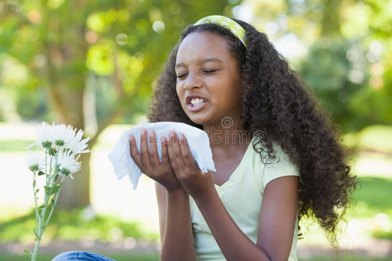 Young girl sitting by flower and sneezing in the park royalty free stock photo