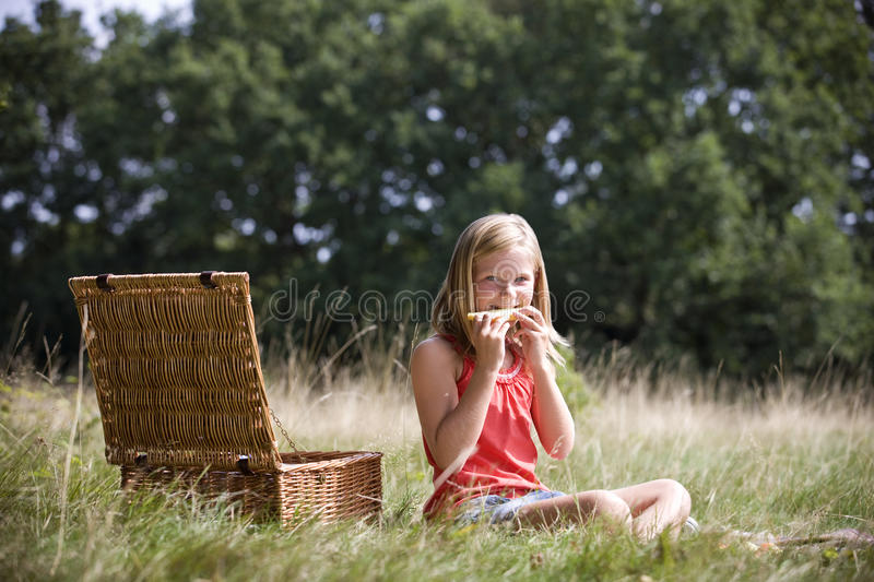 A young girl sitting on the grass, eating melon royalty free stock photo