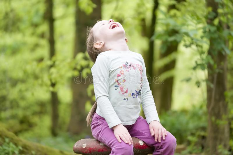 Young girl sitting laughing hands on knees in woodland forest stock image