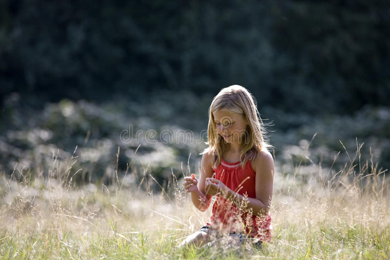 A young girl sitting in long grass, smiling stock photo