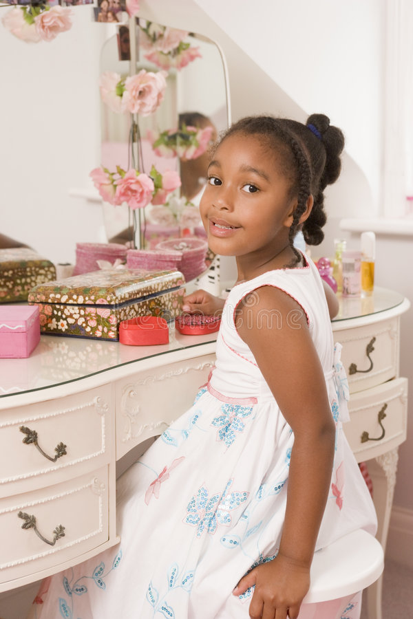 Young girl sitting at mirror in bedroom smiling stock image