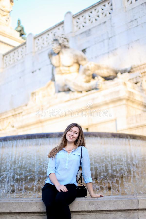 Young girl sitting near Trevi fountain, wearing blue shirt. royalty free stock photography