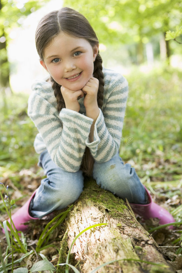 Free Young Girl Sitting On Log Royalty Free Stock Photos - 4789488