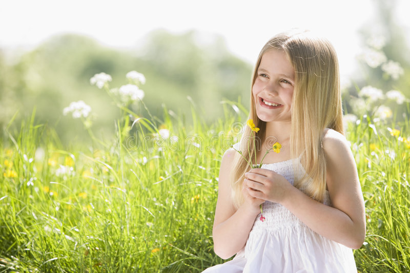 Young Girl Sitting Outdoors Holding Flower Smiling Royalty Free Stock Photography