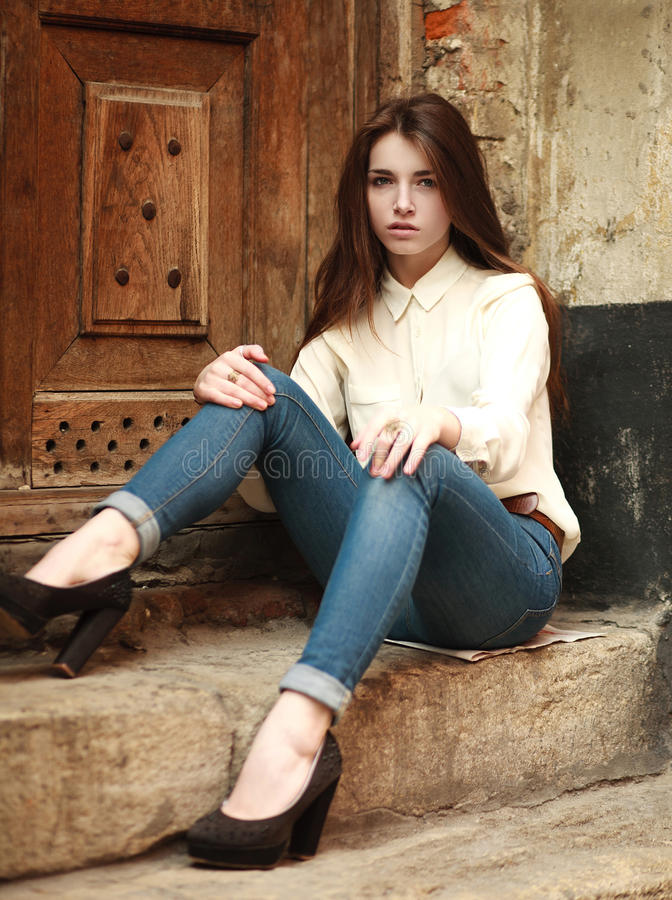 Young girl sitting outdoors sad, on background an old house royalty free stock photography