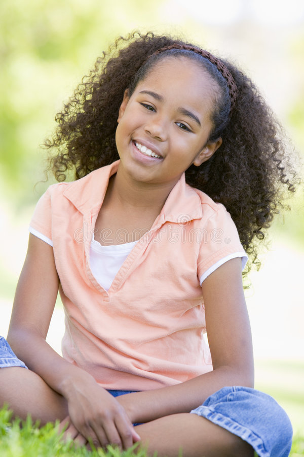 Young girl sitting outdoors smiling stock photo