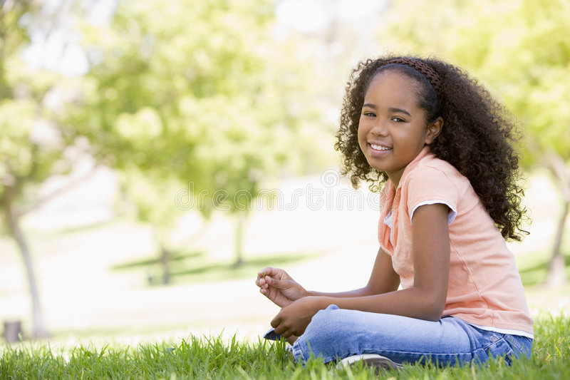 Young girl sitting outdoors smiling stock photos