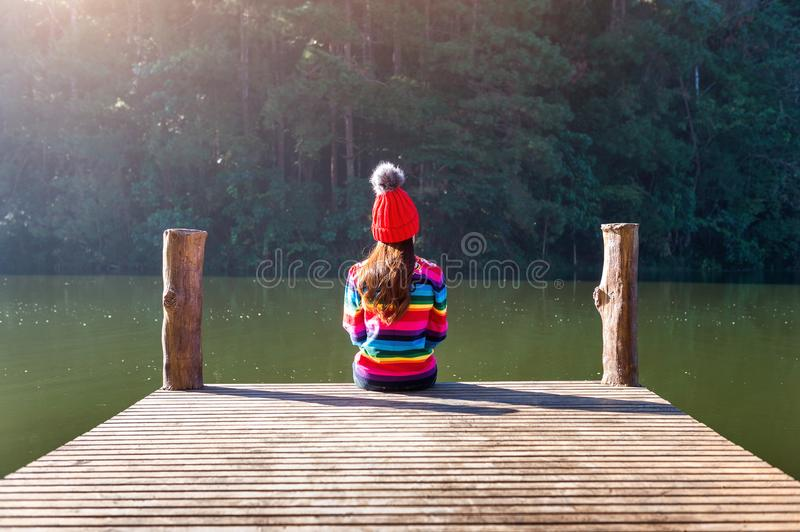 Young girl sitting on a pier stock images