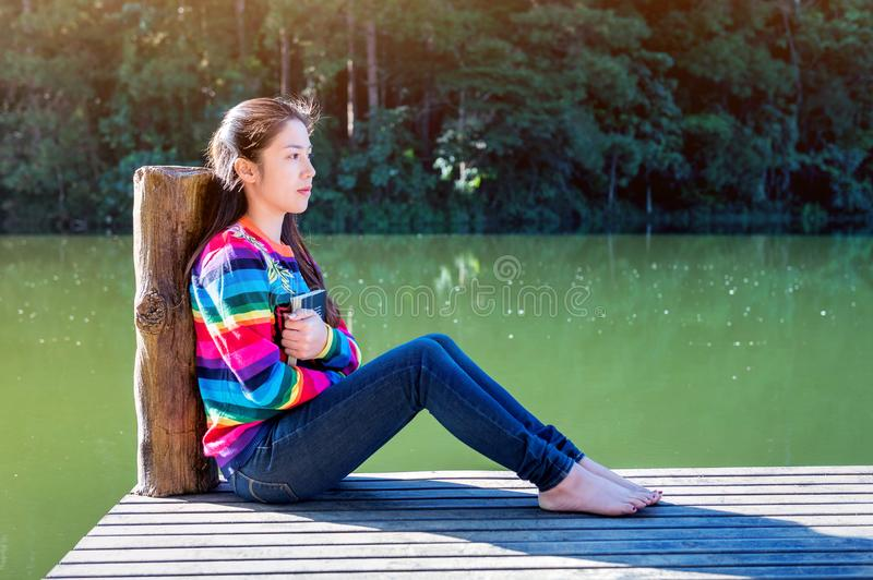 Young girl sitting on a pier. stock image