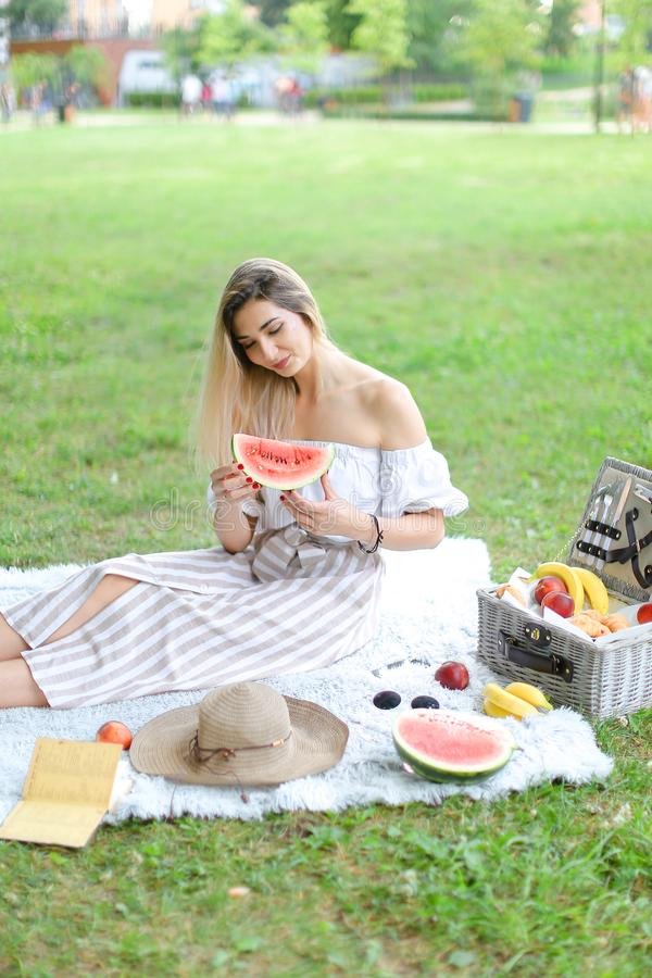 Young girl sitting on plaid near fruits and hat, eating watermelon, grass in background. royalty free stock image