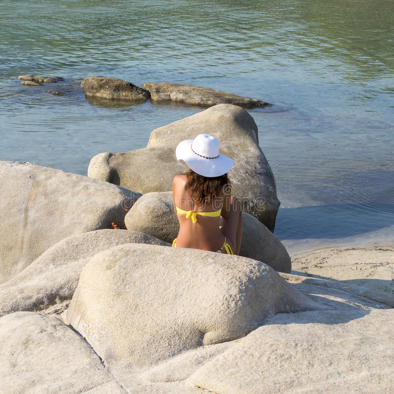 Young girl sitting on the rock stock photo
