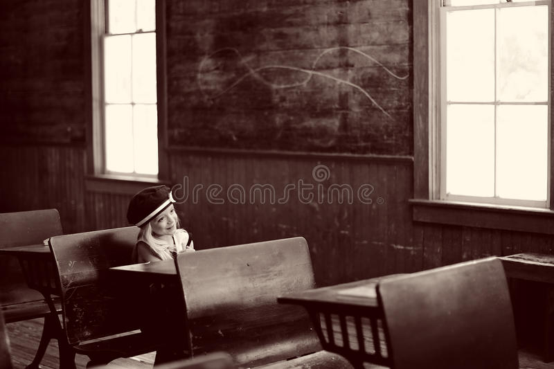 Young girl sitting in school. A young girl sitting in an empty schoolroom stock photos