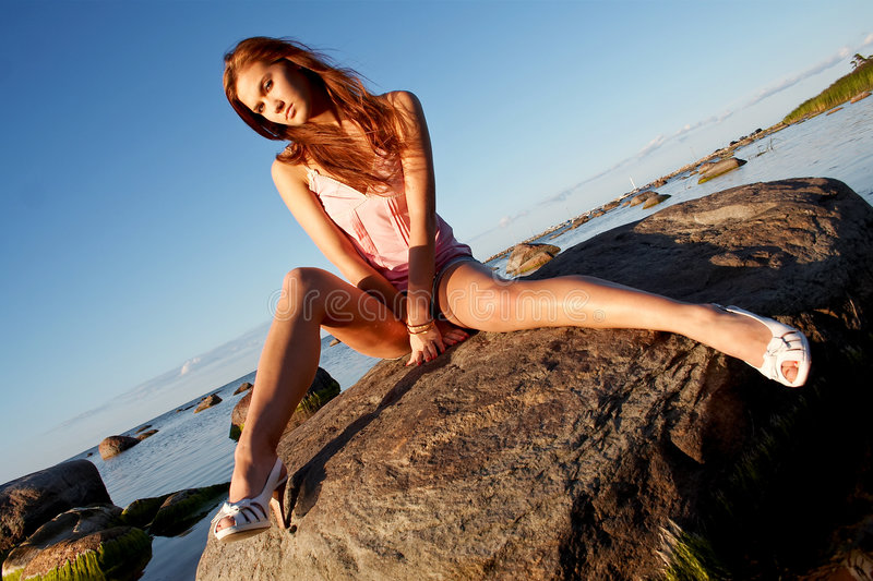 Young girl sitting on a stone royalty free stock image