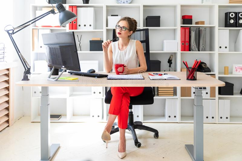 A young girl is sitting at a table in the office, holding a pencil and a red cup in her hands. Beautiful young girl in glasses and a red shirt is working in the stock photos