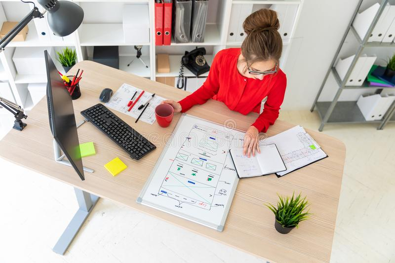 A young girl is sitting at a table in the office, holding a red cup in her hand and looking at the notepad. A magnetic. Beautiful young girl in glasses and a red stock images