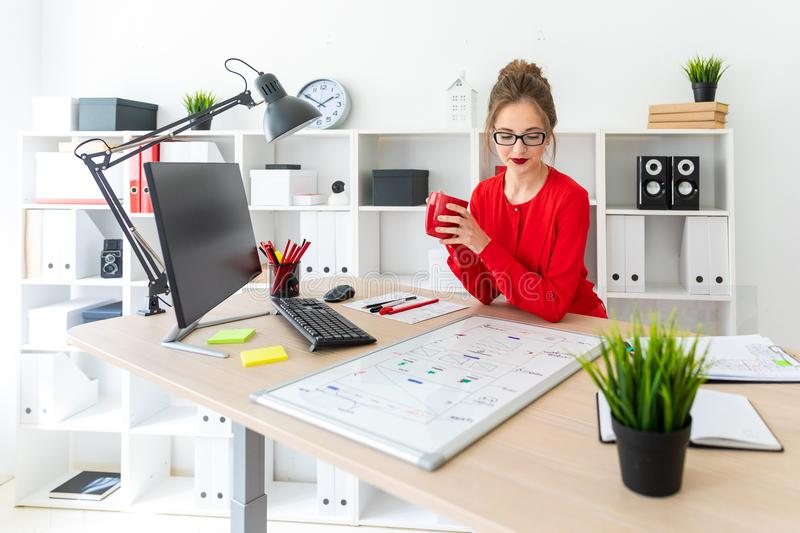 A young girl is sitting at a table in the office, holding a red cup in her hands and looking at a magnetic board. Beautiful young girl in glasses and a red royalty free stock photography