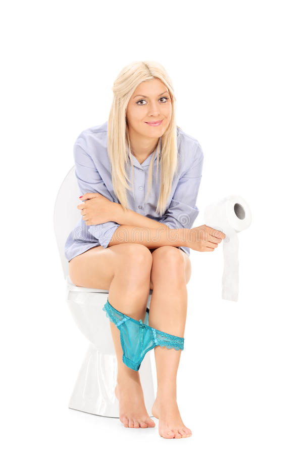 Young Girl Sitting On A Toilet And Holding Toilet Paper