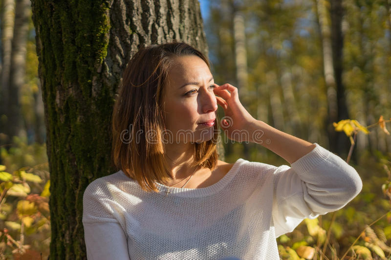Young girl sitting under a tree stock photos