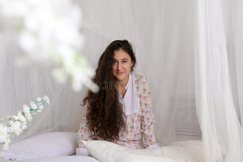 Young girl sitting on a white bed in dress stock image