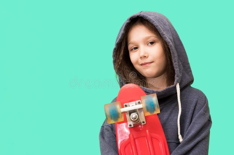 Young girl with skateboard on a blue background. The child holds a skateboard. Brunette little girl with a hood royalty free stock photo