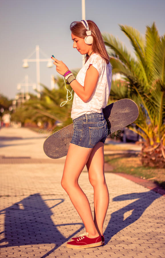 Young girl with skateboard and headphones. Portrait of beautiful young girl with skateboard and headphones listening music in her smartphone outdoors. Warm tones royalty free stock photos