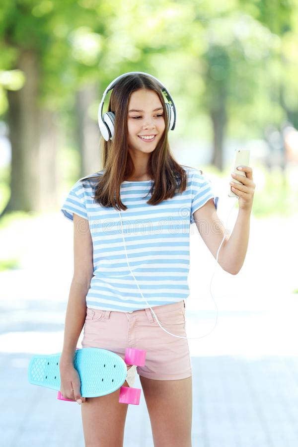 Young girl with skateboard. Headphones and smartphone in the park royalty free stock images