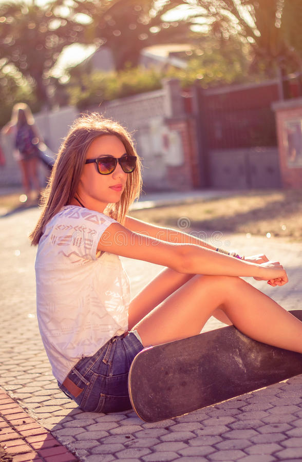 Young girl with skateboard sitting outdoors on. Portrait of beautiful young girl with short shorts and skateboard sitting outdoors on a hot summer day. Warm royalty free stock images