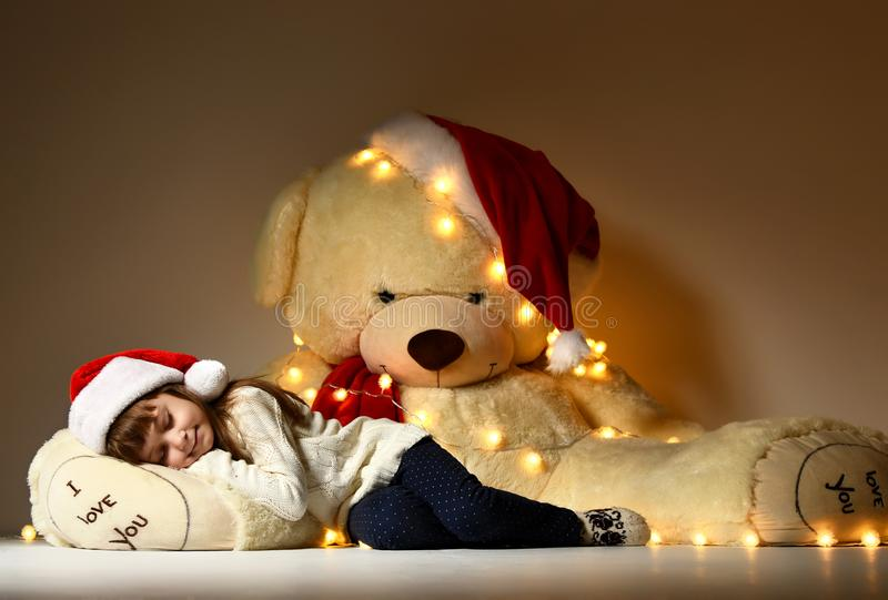 Young girl sleeping with big soft teddy bear toy in christmas santa red hat stock photos
