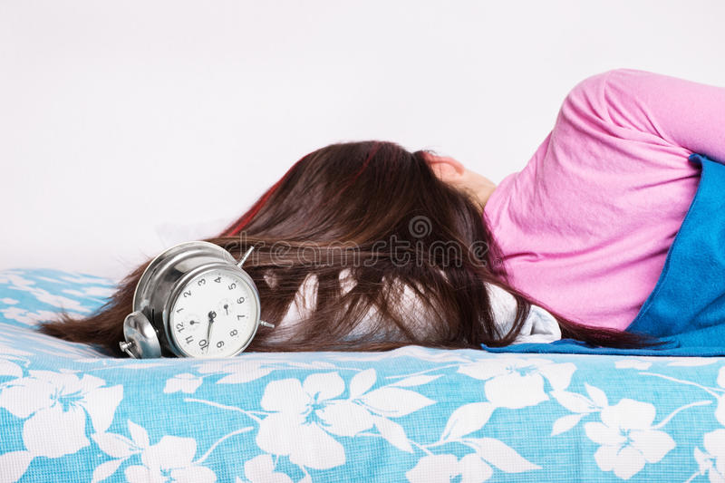 Young girl sleeping while the clock is ringing stock photos