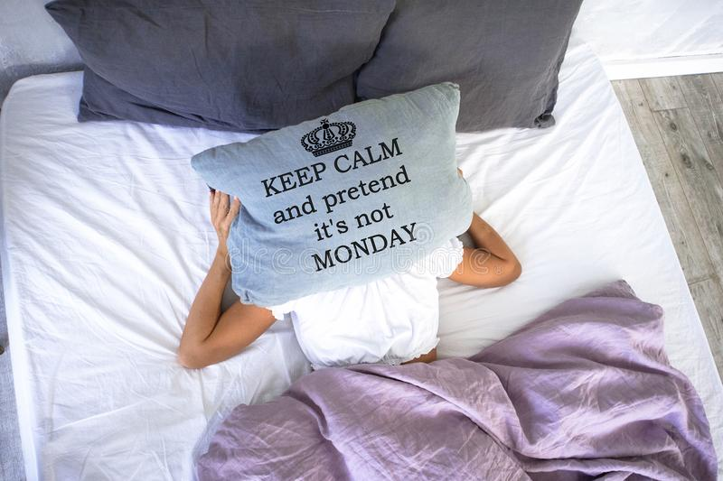 A young girl sleeping doesn`t want to get up ,covering her face with pillow with words keep calm and pretend it is not Monday. royalty free stock photo