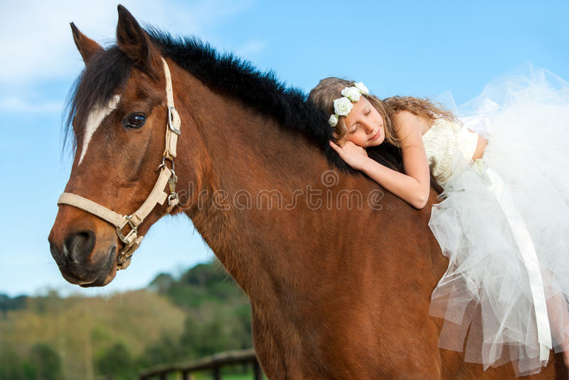 Young girl sleeping on horseback. royalty free stock image