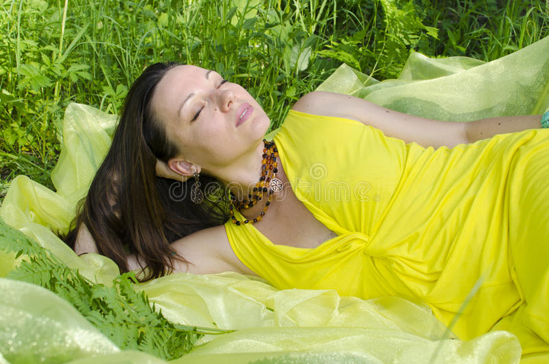 Young girl sleeps on yellow matter in nature stock photos