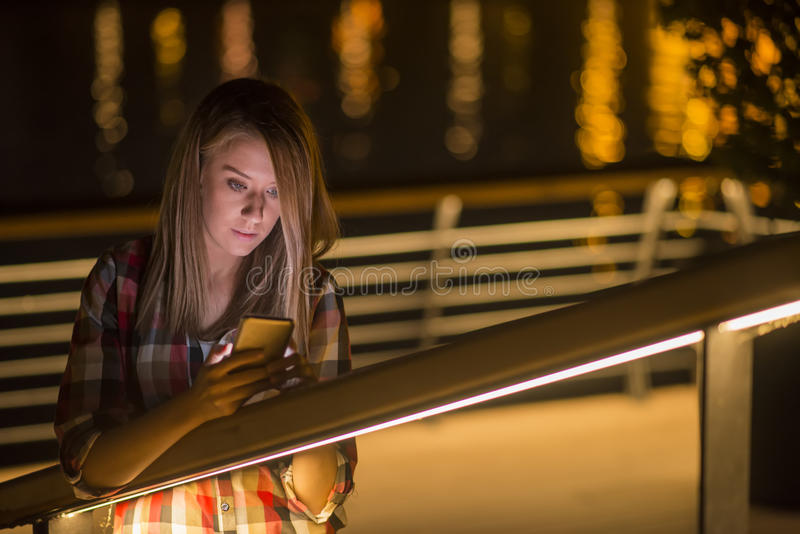 Young girl with smart-phone whatching bad news in internet royalty free stock photo