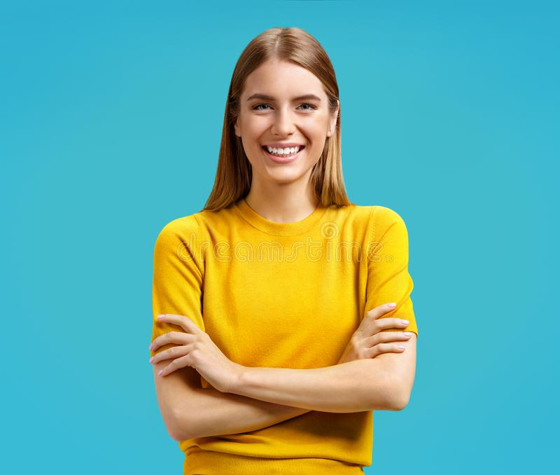 Young girl smiled holds hands crossed, has nice friendly expression. Photo of attractive girl in yellow sweater on blue background royalty free stock image