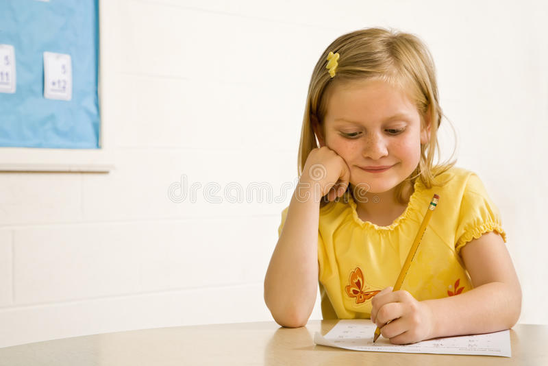 Young Girl Smiling in Classroom Writing on Paper stock photos