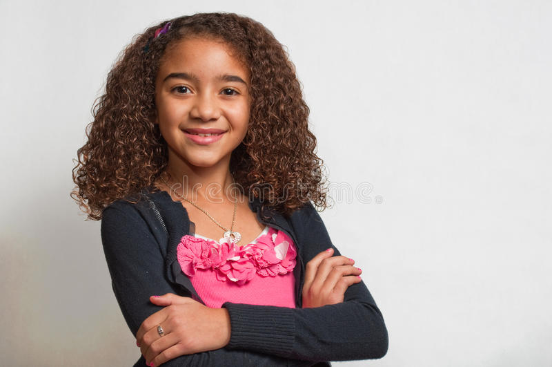 Young girl smiling with folded arms. Young girl smiling with her arms folded, looking at the camera stock photos