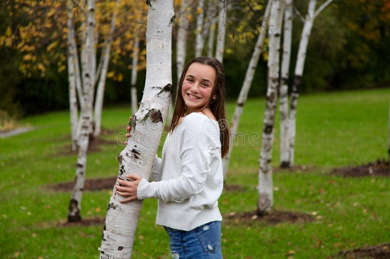 Young girl smiling in a forrest of birch trees royalty free stock photography