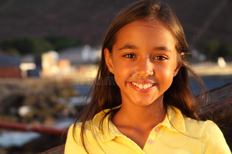 Young girl smiling by seaside in sunset light royalty free stock photography
