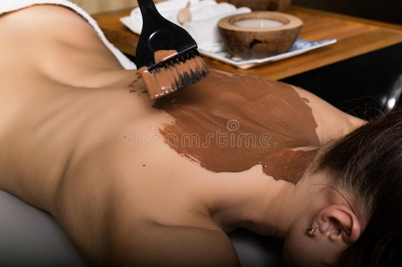 Young girl in the spa salon, chocolate body wrap treatment, skin rejuvenation. Beauty treatment concept stock image