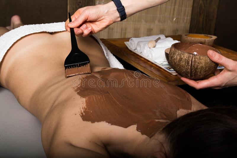 Young girl in the spa salon, chocolate body wrap treatment, skin rejuvenation. Beauty treatment concept royalty free stock photos