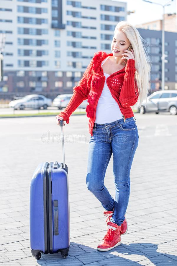 Young girl speaks by mobile phone. Suitcase. The concept of travel, work, lifestyle. stock image