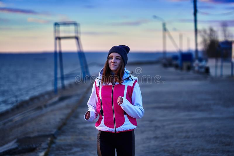 A young girl in a sports hat and jacket makes a morning jog on the embankment in the morning before the dawn of the sun. A colder autumn morning royalty free stock images