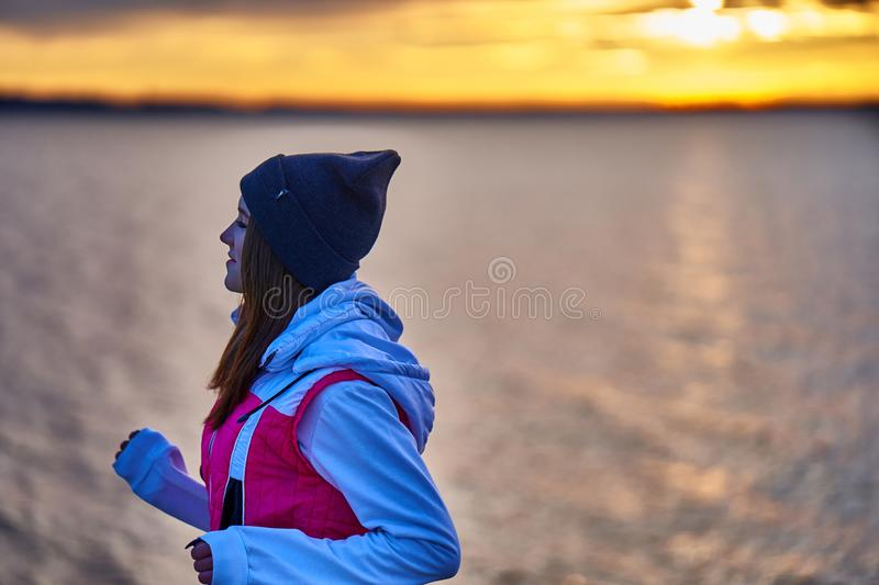 A young girl in a sports hat and jacket makes a morning jog on the embankment in the morning before the dawn of the sun. A colder autumn morning stock photo