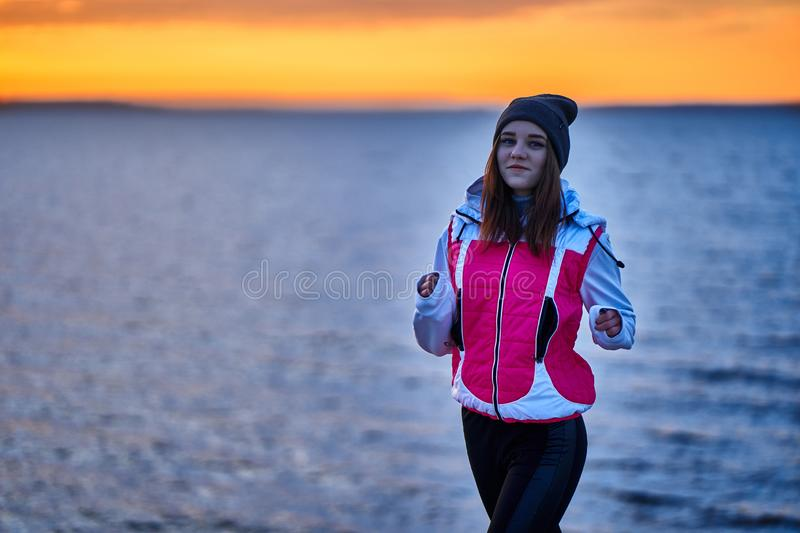 A young girl in a sports hat and jacket makes a morning jog on the embankment in the morning before the dawn of the sun. A colder autumn morning stock images