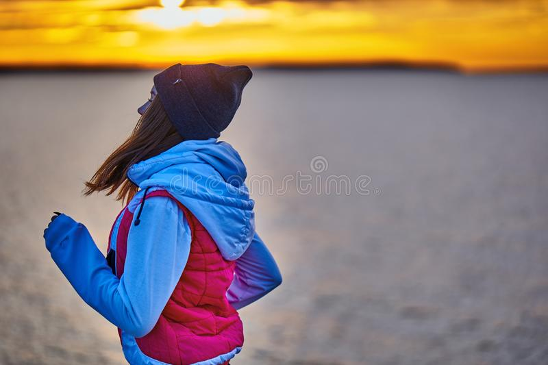A young girl in a sports hat and jacket makes a morning jog on the embankment in the morning before the dawn of the sun. A colder autumn morning stock photography