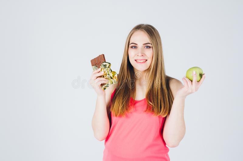 Girl chooses between Apple and chocolate stock image