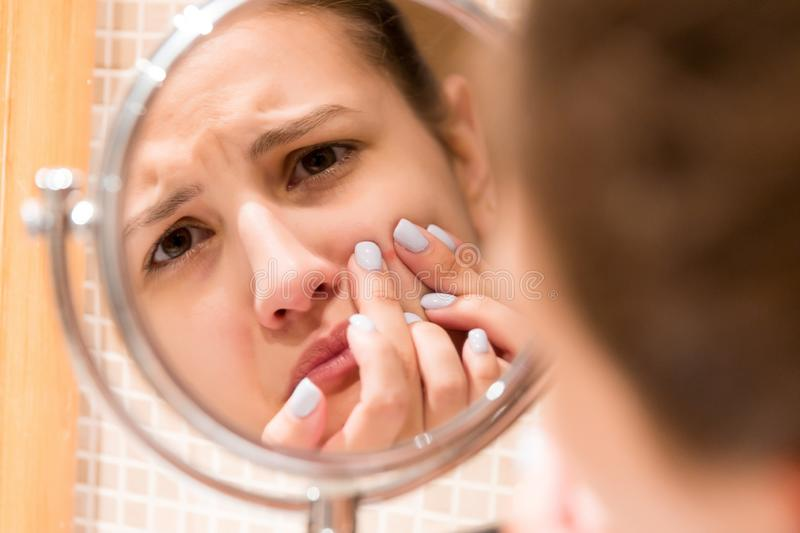 Young girl squeezes pimple on the fer face in front of a bathroom mirror. Beauty skincare and wellness morning concept.  royalty free stock image